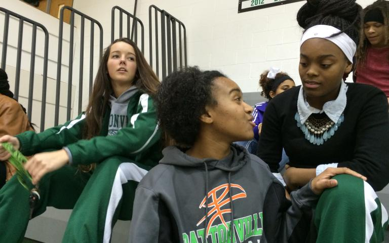 Pattonville High School basketball players (left to right) Cassie Callahan, Allyson Sanders, and Tyra Brown watch the B-squad before a home game in Maryland Heights, Missouri. Photo by John Biewen.