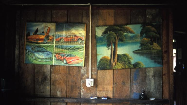 The wall of a house in the village of Kampung Terian reveals the owner's taste in fast cars and landscapes.