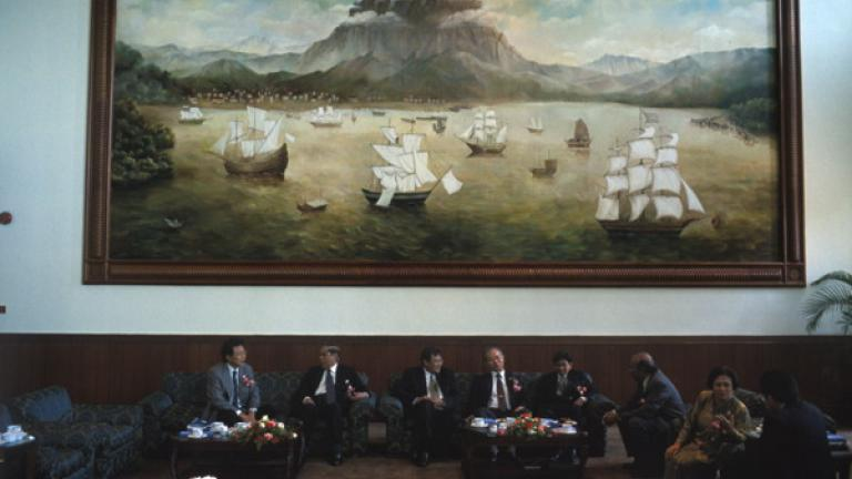 Human rights lawyers break for coffee at the five-star Sutera Harbour Resort in Kota Kinabalu during a conference focused on human rights complaints against the rural communities.  A contemporary painting of the colonial city of Kota Kinabalu (known as Jesselton during British rule) with Mount Kinabalu in the background hangs on the hotel wall.
