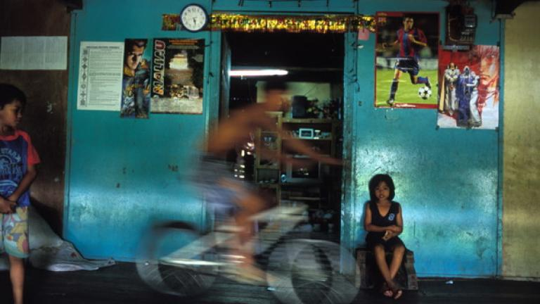 A boy bikes along the corridor of a state-built Rungus longhouse near Kudat.   The Rungus are one of the most traditional ethnic groups in Sabah. Each of the compartments in a Rungus longhouse is seen as a family home; this living arrangement is thought to have arisen from the need for safety during times of tribal fighting and head-hunting.