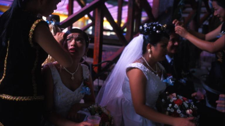 Members of a bridal party in Kampung Nampasan, Penampang, have their hair checked for rice and confetti after they arrive at the husband's family home. The wedding party then continued on to Kampung Tiga, a twelve-hour walk away, for a week-long party at the bride's family home.