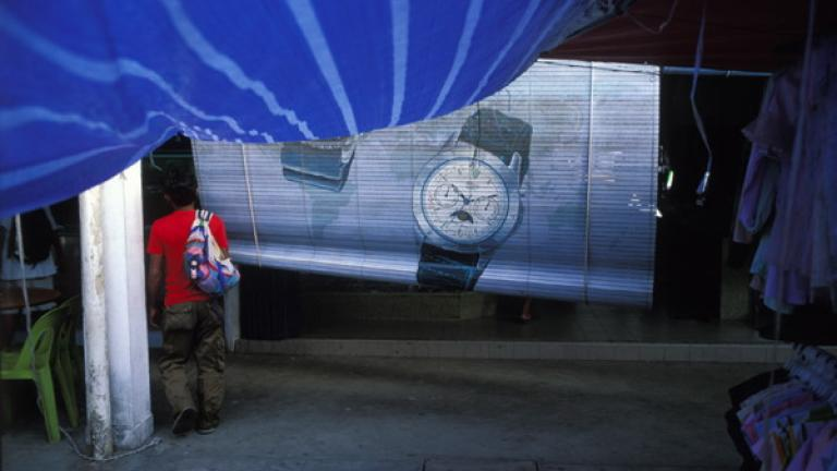 A man walks past a sign for a watch store in Donggongon, Penampang.