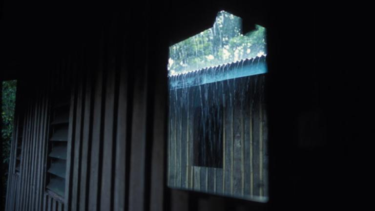 A mirror reflects a seasonal downpour in Kampung Tiga, Bundu.