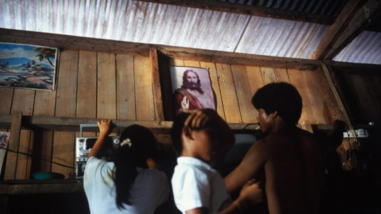 At a house in Kampung Tiong, Bundu, a family goes about their activities below a picture of Jesus.  While Christianity has entered the life of many villages, traditional beliefs form a large part of indigenous identity.