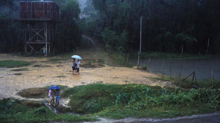Girls search for shelter during a seasonal downpour in a village outside of Donggongon.
