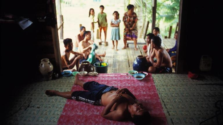 In Tongod, a man recovers from a hangover in front of his family.   Inhabitants of remote villages often have time on their hands, and alcohol is a frequent means of reducing boredom.