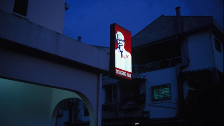 A Kentucky Fried Chicken sign glows against the evening sky in Donggongon, Penampang.   Fast food is popular but considered expensive by villagers in rural communities.