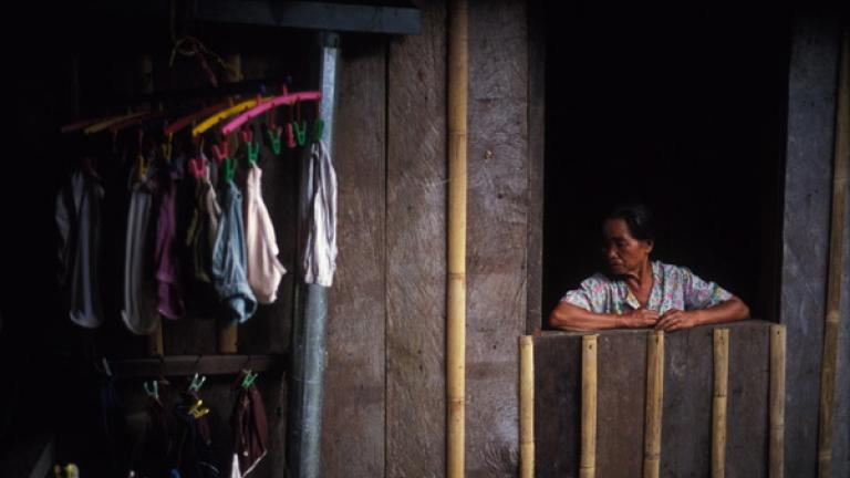 In Kampung Terian, a woman stands at her window.