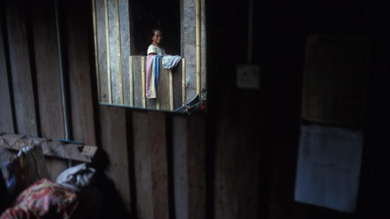 In Kampung Terian, a woman at her window is reflected in a mirror.