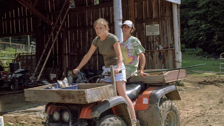 Amy Ager and a farmhand on a four-wheeler at Hickory Nut Gap Farm. Amy and Jamie Ager started Hickory Nut Gap Farm's natural meats business in 2003. June 2006. Photo by Ken Abbott.