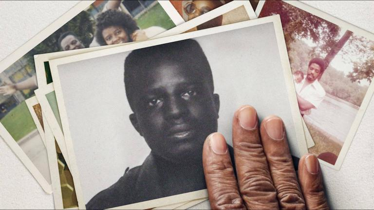 A hand resting on a printed portrait of a Black boy.