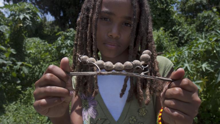 Tsehaye displays an empty pod shell she discovered on a walk around Lake Tana.