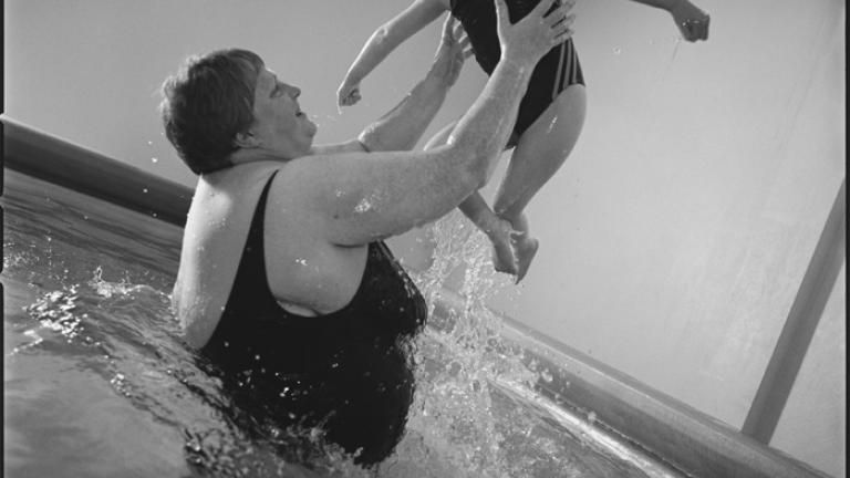 Helda lifts Eydís in the pool, Lyngas, Reykjavik, Iceland 2006