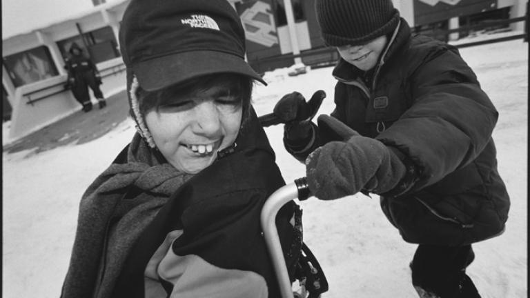 Hrafn pushes Alexander's wheelchair in the snow, Öskjuhlíðarskóli, Reykjavik, Iceland 2007