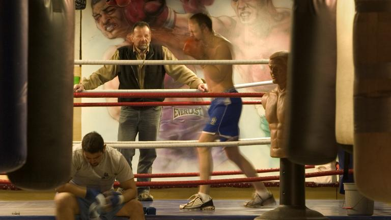 Trainer Mike Vukelic watches Sean Dewitt shadow box while Eddie Corado wraps his hands, Fraser Arms Boxing Club, Vancouver, British Columbia, 2004