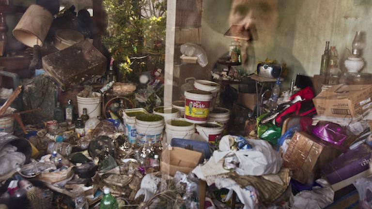 "Photograph from ""House of Charm"" by Jessica Eve Rattner, winner of the 2016 CDS Documentary Essay Prize in Photography. Lee is reflected in a window of her house, Berkeley, California, 2009. Soon after this image was made, her son cleaned out the house, filling six dumpsters."