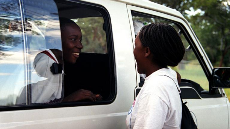 Patience and Marvel, both youth group leaders, greet each other as a vanload of youth arrives at a CPS event held outside Harare. Photograph by Lucy Wilson.