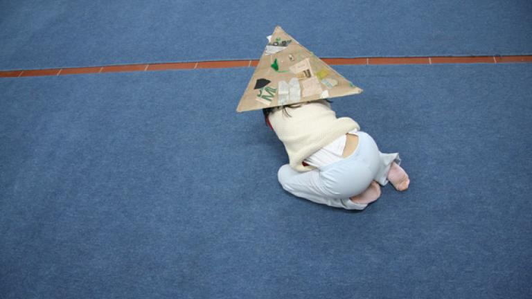 A child plays alone while wearing her pyramid hat.