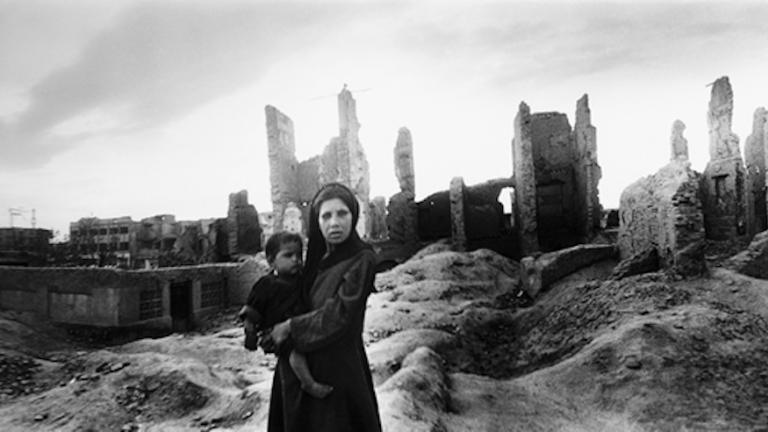An Afghan woman holds her child in front of building ruins in Kabul. Afghanistan, 2002