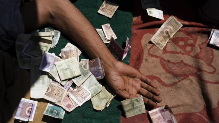 A Uighur beggar lays amid a pile of Chinese money outside a mosque at prayer time, Kashgar, Xinjiang Uighur Autonomous Region, China, 2007