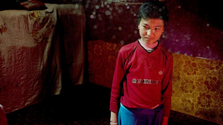 A Uighur girl in her home seen through the dust in a beam of sunlight, Kashgar, Xinjiang Uighur Autonomous Region, China, 2007