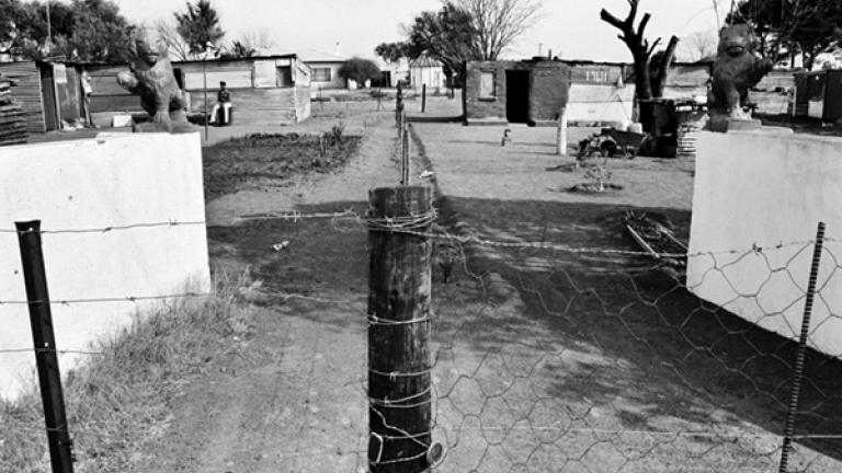 The former entry to an Afrikaner-owned farm is divided down the middle where two housing sites meet.