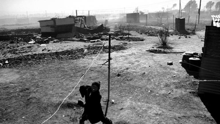 A nine-year-old boy kicks a bottle tied to the end of a rope. He is visiting his mother during school vacation but will return to his grandparents' home several hundred kilometers away at the end of his two-week stay. His mother is unemployed, and his father is in Johannesburg looking for work.