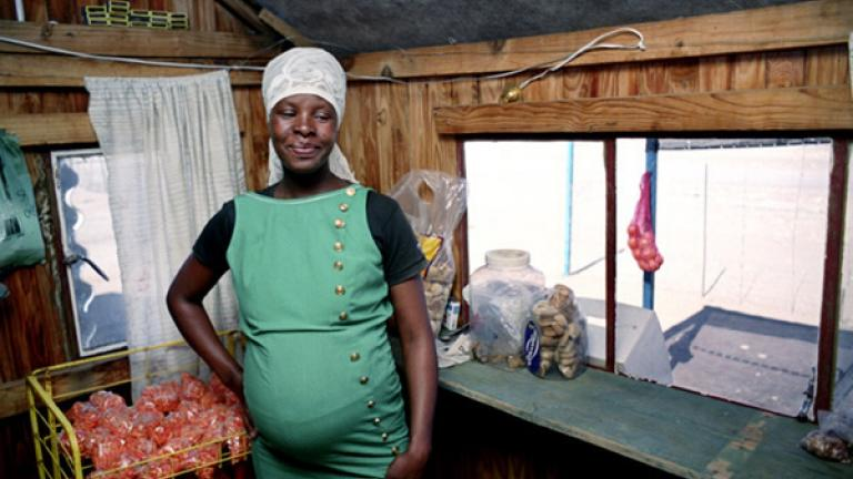 Margaret, seven months pregnant, in her shop where she sells fruits and vegetables, snacks, paraffin, and other staples