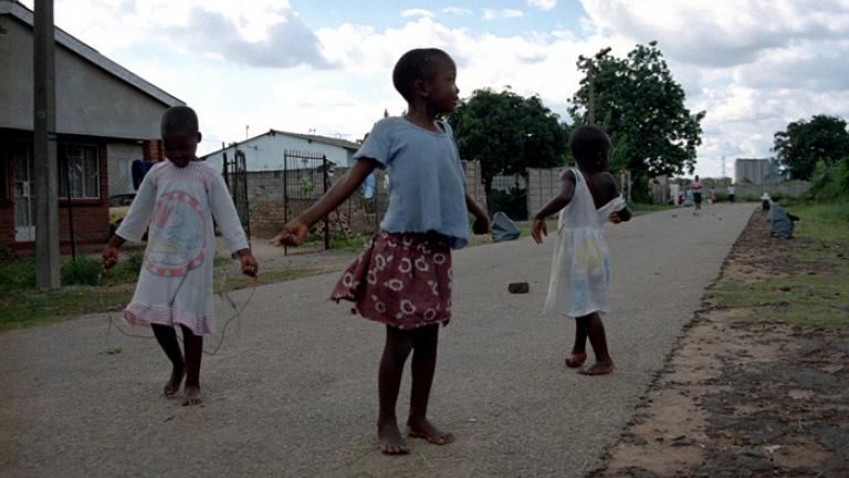 Three young girls enjoy an afternoon spent playing with jump ropes made from grass. Photograph by Lucy Wilson.
