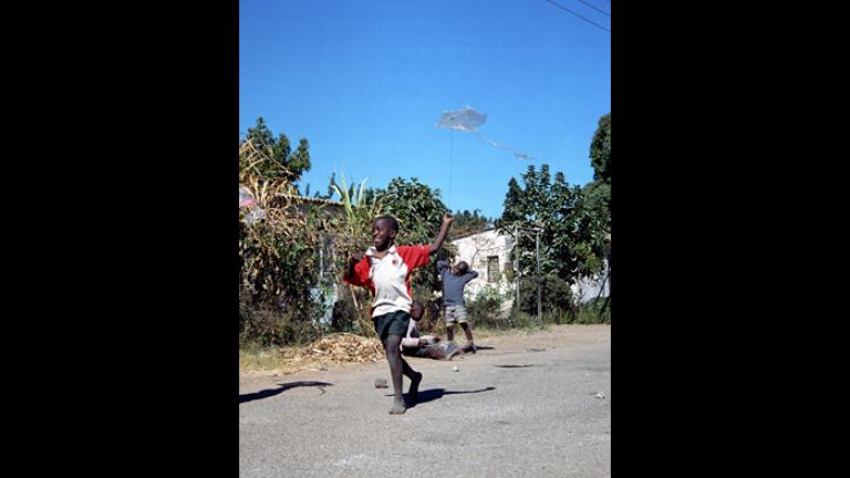 A barefoot boy runs down his street with a homemade kite. Photograph by Lucy Wilson.