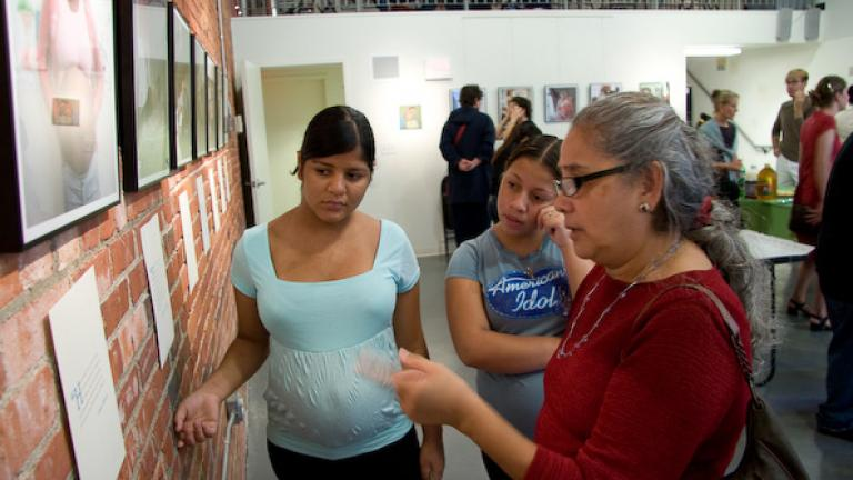 At the exhibit opening, Martha, a Roca staff member who works with young mothers, reads an interview quote with two of her participants.