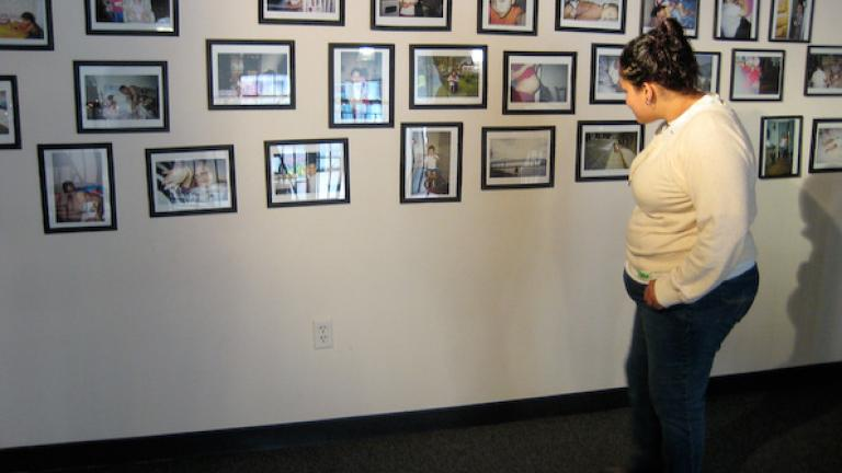 Roxannie looks for her photographs on a wall of photographs that were taken by the young mothers.
