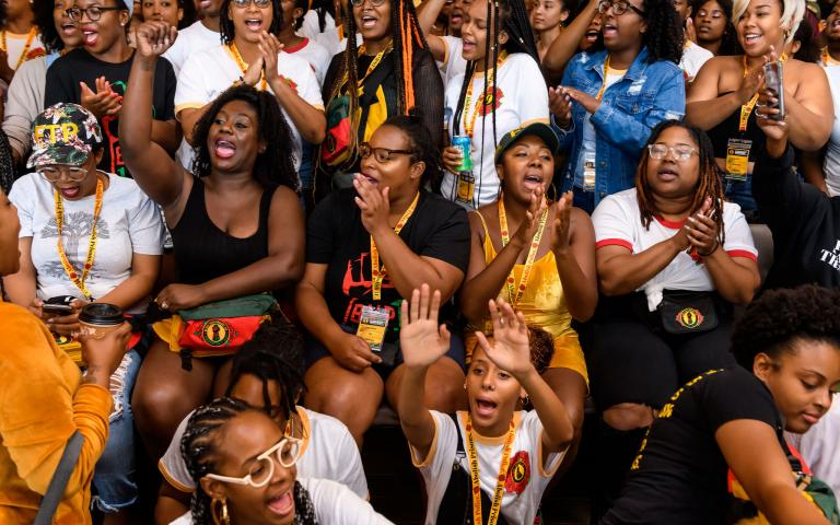 Image shows a crowd of black women at a Black Youth Project 100 convening. Photo by Christopher Jason