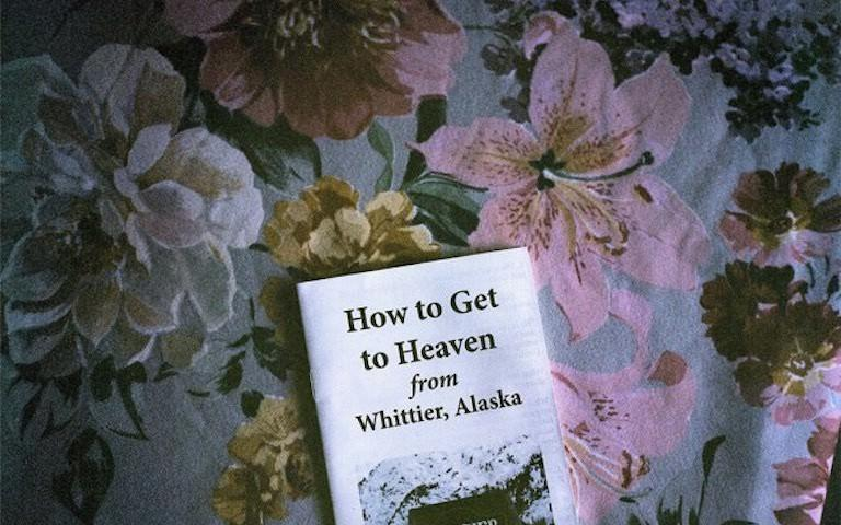 "A photo of a pamphlet sitting on top of a flowery tablecloth. The pamphlet reads ""How to Get to Heaven from Whittier, Alaska"""