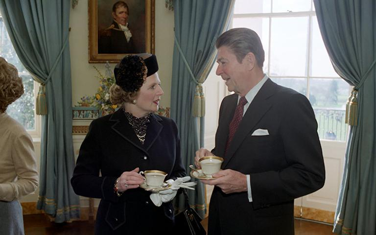 A photo of Margaret Thatcher and Ronald Reagan holding teacups and talking to each other.