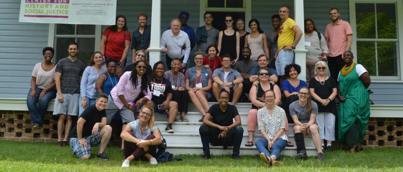 A group photo of participants from the 2018 NEH Institute at Duke sitting on a porch.