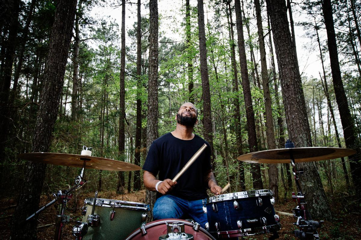 A photo of a young man playing drums outside in a forest