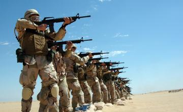 A line of american soldiers pointing guns to the right of frame.