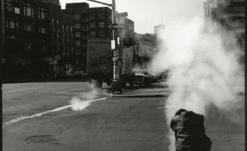 A black and white photo of a man sitting on a curb in front of a plume of steam from a grate, by Sylvia Plachy